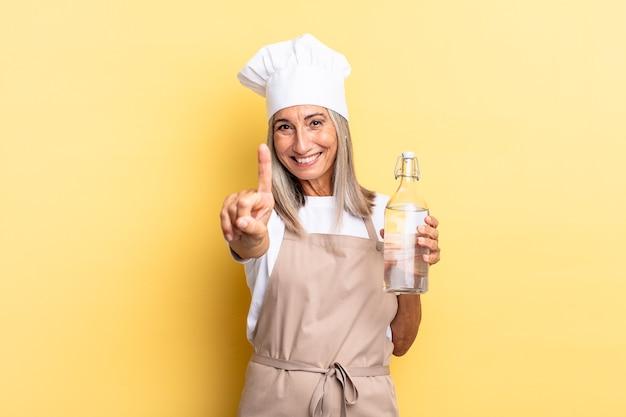 Chef-kokvrouw van middelbare leeftijd die trots en zelfverzekerd glimlacht en nummer één triomfantelijk poseert, zich een leider voelend met een waterfles