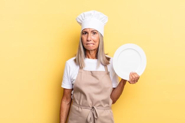 Chef-kokvrouw van middelbare leeftijd die verbaasd en verward kijkt, lip bijt met een nerveus gebaar, het antwoord op het probleem niet weet en een gerecht vasthoudt