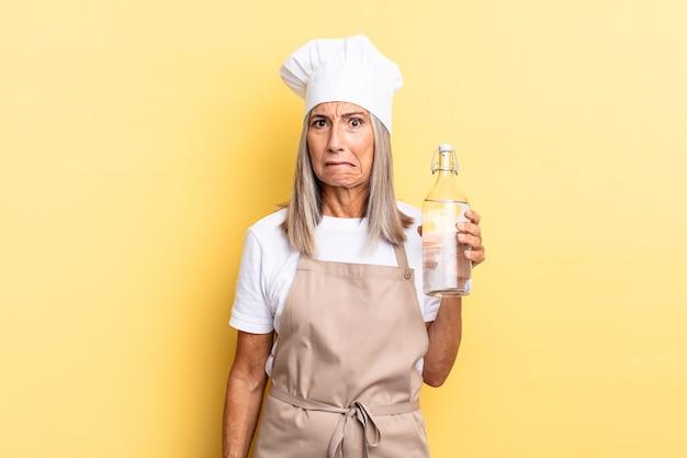 Chef-kokvrouw van middelbare leeftijd die verbaasd en verward kijkt, lip bijt met een nerveus gebaar, niet wetend het antwoord op het probleem met een waterfles