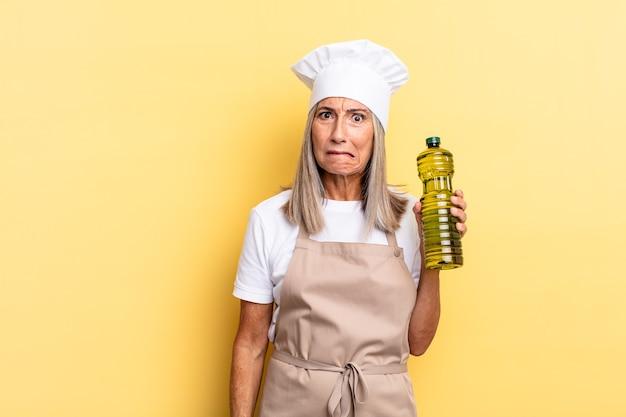 Chef-kokvrouw van middelbare leeftijd die verbaasd en verward kijkt, lip bijt met een nerveus gebaar, niet wetend het antwoord op het probleem