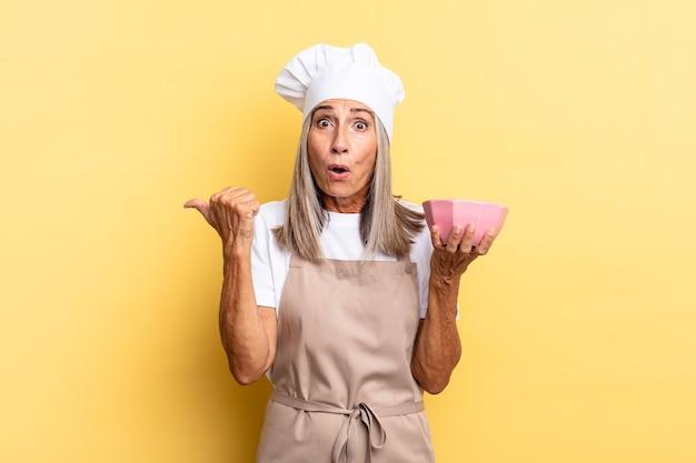 Chef-kokvrouw van middelbare leeftijd die verbaasd kijkt in ongeloof, wijst naar een object aan de zijkant en zegt wauw, ongelooflijk en een lege pot vasthoudt