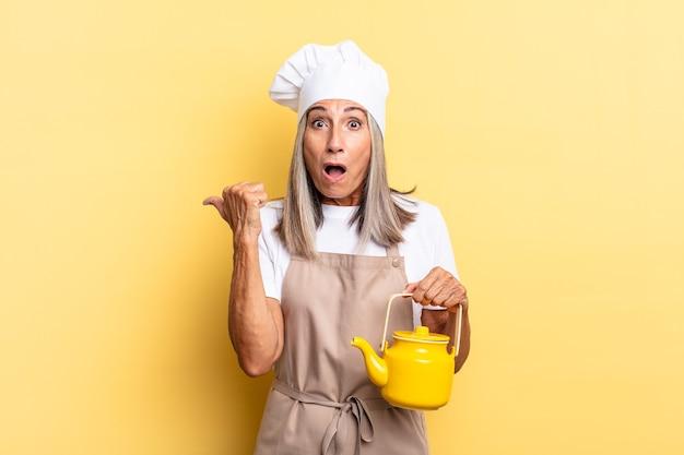 Chef-kokvrouw van middelbare leeftijd die verbaasd kijkt in ongeloof, wijst naar een object aan de zijkant en zegt wow, ongelooflijk en een theepot vasthoudt