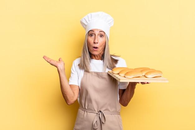 Chef-kokvrouw van middelbare leeftijd die verrast en geschokt kijkt, met open mond terwijl ze een object vasthoudt met een open hand aan de zijkant en een broodblad vasthoudt