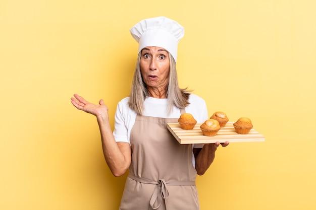 Chef-kokvrouw van middelbare leeftijd die verrast en geschokt kijkt, met open mond terwijl ze een object vasthoudt met een open hand aan de zijkant en een dienblad met muffins vasthoudt