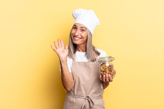 Chef-kokvrouw van middelbare leeftijd die vrolijk en opgewekt lacht, met de hand zwaait, je verwelkomt en begroet, of afscheid neemt met koekjes