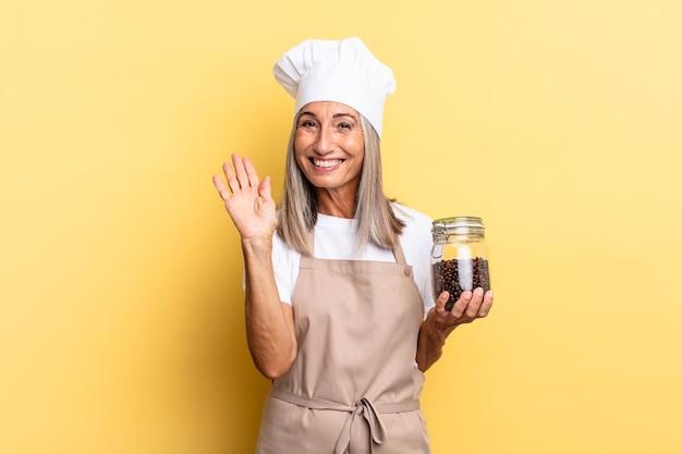 Chef-kokvrouw van middelbare leeftijd die vrolijk en opgewekt lacht, met de hand zwaait, je verwelkomt en begroet, of vaarwel zegt met koffiebonen