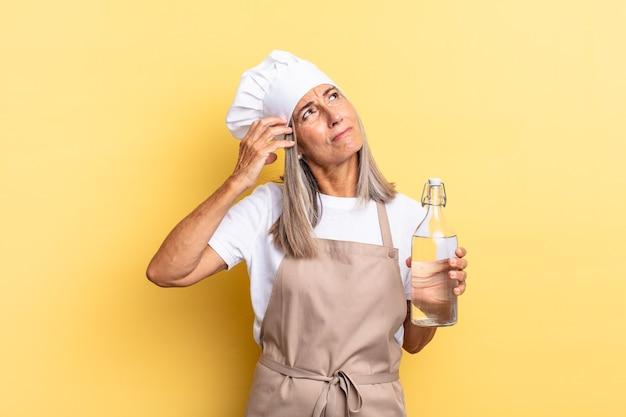 Chef-kokvrouw van middelbare leeftijd die vrolijk lacht en dagdroomt of twijfelt, opzij kijkend met een waterfles