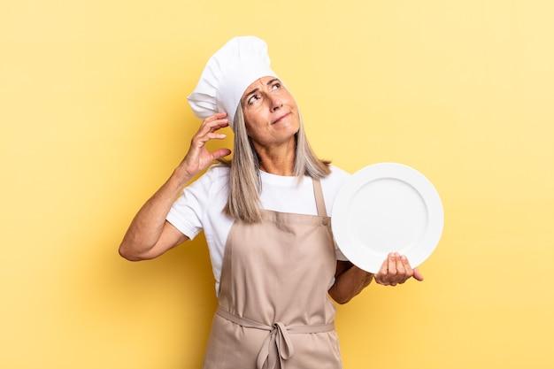 Chef-kokvrouw van middelbare leeftijd die vrolijk lacht en dagdroomt of twijfelt, opzij kijkt en een gerecht vasthoudt