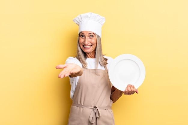 Chef-kokvrouw van middelbare leeftijd die vrolijk lacht met een vriendelijke, zelfverzekerde, positieve blik, een object of concept aanbiedt en toont en een gerecht vasthoudt