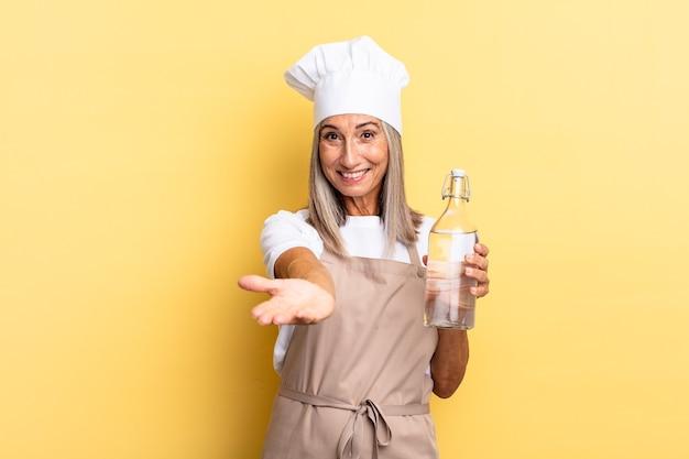 Chef-kokvrouw van middelbare leeftijd die vrolijk lacht met een vriendelijke, zelfverzekerde, positieve blik, een object of concept aanbiedt en toont met een waterfles