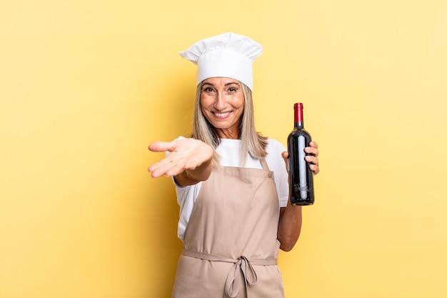 Chef-kokvrouw van middelbare leeftijd die vrolijk lacht met een vriendelijke, zelfverzekerde, positieve blik, een object of concept aanbiedt en toont met een wijnfles