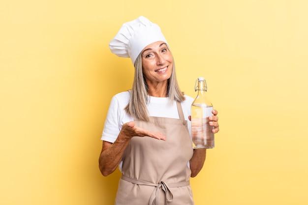 Chef-kokvrouw van middelbare leeftijd die vrolijk lacht, zich gelukkig voelt en een concept in kopieerruimte toont met een handpalm met een waterfles