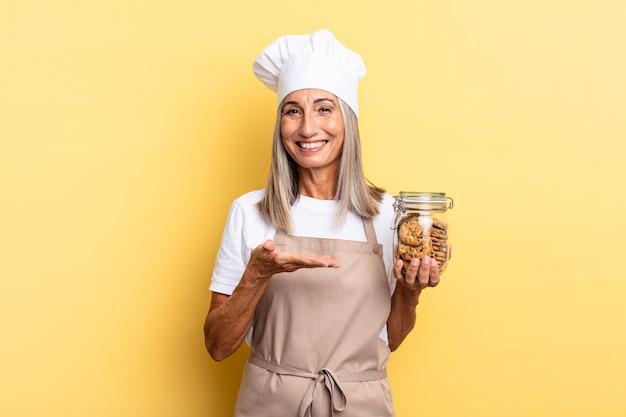Chef-kokvrouw van middelbare leeftijd die vrolijk lacht, zich gelukkig voelt en een concept in kopieerruimte toont met een handpalm met koekjes