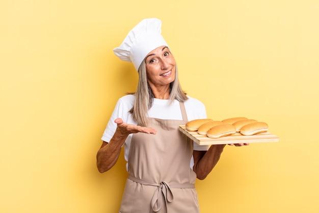 Chef-kokvrouw van middelbare leeftijd die vrolijk lacht, zich gelukkig voelt en een concept in kopieerruimte toont met palm van hand en een broodblad vasthoudt