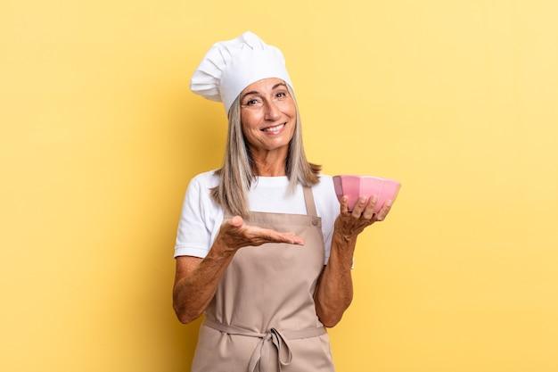 Chef-kokvrouw van middelbare leeftijd die vrolijk lacht, zich gelukkig voelt en een concept in kopieerruimte toont met palm van hand en een lege pot vasthoudt
