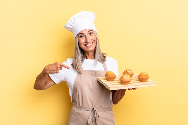 Chef-kokvrouw van middelbare leeftijd die vrolijk lacht, zich gelukkig voelt en naar de zijkant en naar boven wijst, een object in de kopieerruimte laat zien en een dienblad met muffins vasthoudt