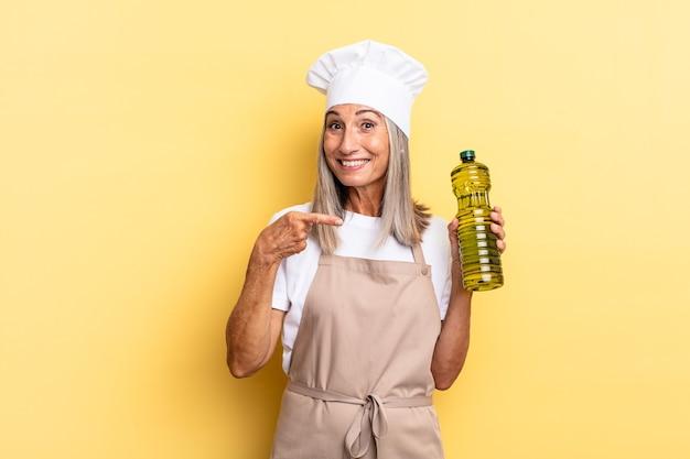 Chef-kokvrouw van middelbare leeftijd die vrolijk lacht, zich gelukkig voelt en naar de zijkant en naar boven wijst, een object in de kopieerruimte laat zien