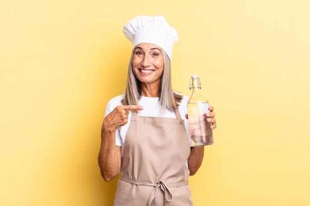 Chef-kokvrouw van middelbare leeftijd die vrolijk lacht, zich gelukkig voelt en naar de zijkant en naar boven wijst, een object in de kopieerruimte toont met een waterfles