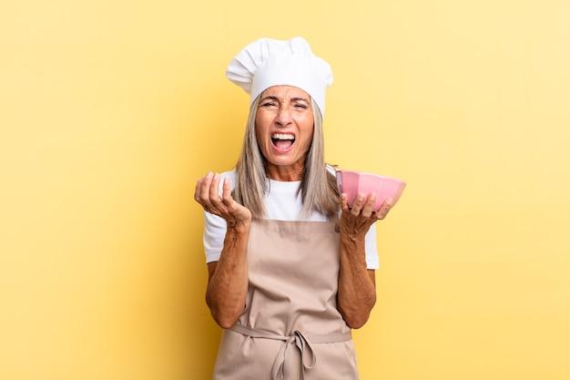 Chef-kokvrouw van middelbare leeftijd die wanhopig en gefrustreerd, gestrest, ongelukkig en geïrriteerd kijkt, schreeuwt en schreeuwt en een lege pot vasthoudt