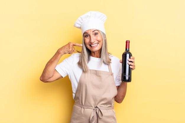 Chef-kokvrouw van middelbare leeftijd die zelfverzekerd glimlacht en wijst naar een brede glimlach, positieve, ontspannen, tevreden houding met een wijnfles