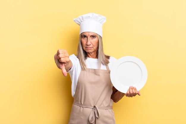 Chef-kokvrouw van middelbare leeftijd die zich boos, boos, geïrriteerd, teleurgesteld of ontevreden voelt, duimen naar beneden toont met een serieuze blik en een gerecht vasthoudt