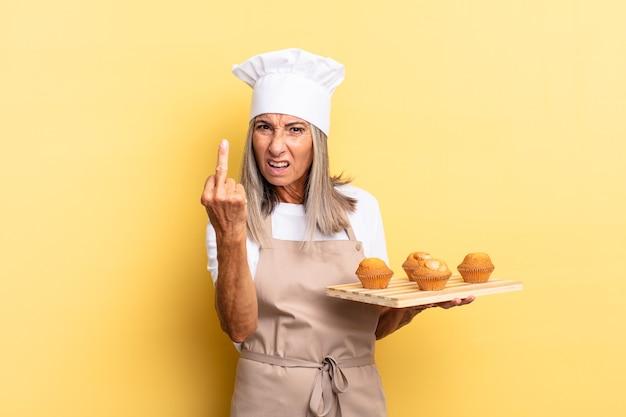Chef-kokvrouw van middelbare leeftijd die zich boos, geïrriteerd, opstandig en agressief voelt, de middelvinger omdraait, terugvecht en een dienblad met muffins vasthoudt