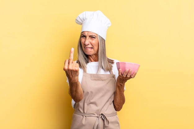 Chef-kokvrouw van middelbare leeftijd die zich boos, geïrriteerd, opstandig en agressief voelt, de middelvinger omdraait, terugvecht en een lege pot vasthoudt