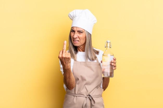 Chef-kokvrouw van middelbare leeftijd die zich boos, geïrriteerd, opstandig en agressief voelt, de middelvinger omdraait, terugvecht met een waterfles