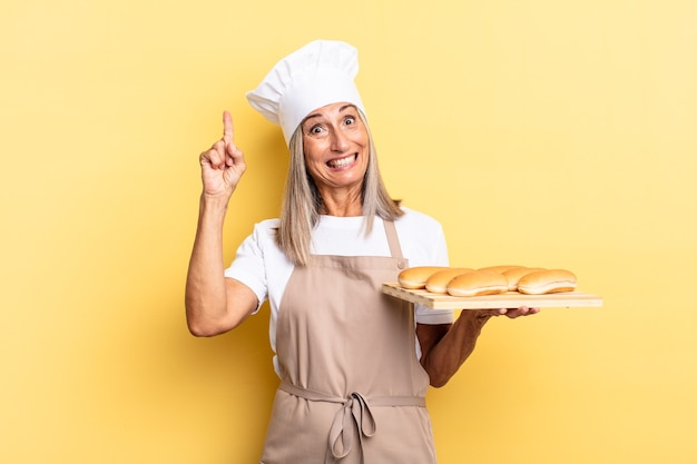 Chef-kokvrouw van middelbare leeftijd die zich een gelukkig en opgewonden genie voelt na het realiseren van een idee, vrolijk de vinger opstekend, eureka! en een broodblad vasthouden Premium Foto