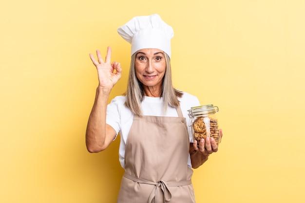 Chef-kokvrouw van middelbare leeftijd die zich gelukkig, ontspannen en tevreden voelt, goedkeuring toont met een goed gebaar, glimlachend met koekjes