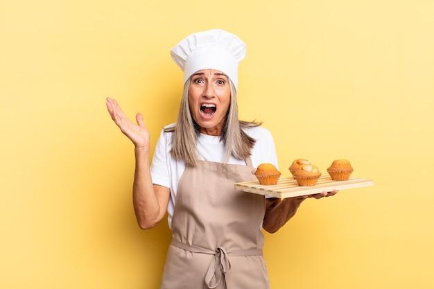 Chef-kokvrouw van middelbare leeftijd die zich gelukkig, opgewonden, verrast of geschokt voelt, glimlacht en verbaasd is over iets ongelooflijks en een dienblad met muffins vasthoudt