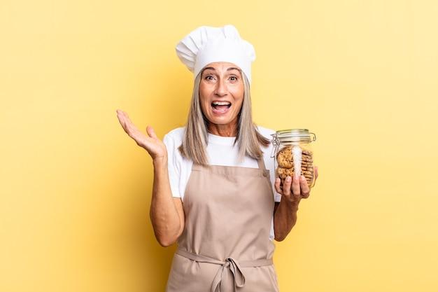 Chef-kokvrouw van middelbare leeftijd die zich gelukkig, opgewonden, verrast of geschokt voelt, glimlacht en verbaasd is over iets ongelooflijks met koekjes