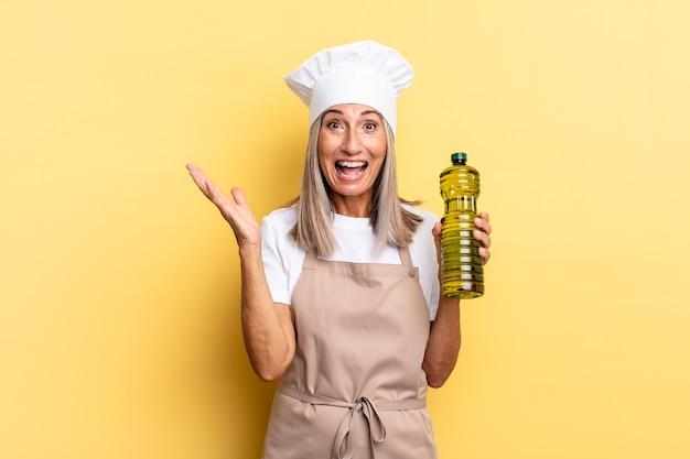 Chef-kokvrouw van middelbare leeftijd die zich gelukkig, opgewonden, verrast of geschokt voelt, glimlacht en verbaasd over iets ongelooflijks