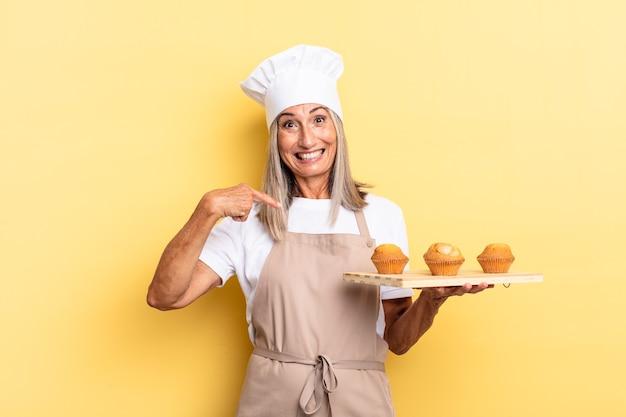 Chef-kokvrouw van middelbare leeftijd die zich gelukkig, verrast en trots voelt, naar zichzelf wijst met een opgewonden, verbaasde blik en een dienblad met muffins vasthoudt