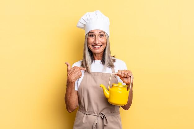 Chef-kokvrouw van middelbare leeftijd die zich gelukkig, verrast en trots voelt, naar zichzelf wijst met een opgewonden, verbaasde blik en een theepot vasthoudt
