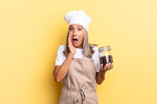 Chef-kokvrouw van middelbare leeftijd die zich geschokt en bang voelt, er doodsbang uitziet met open mond en handen op de wangen met koffiebonen