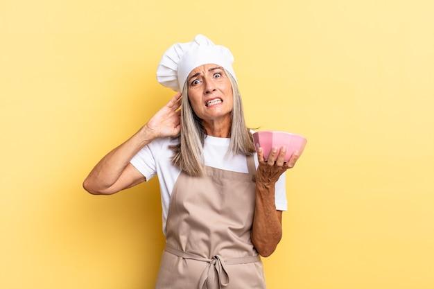 Chef-kokvrouw van middelbare leeftijd die zich gestrest, bezorgd, angstig of bang voelt, met de handen op het hoofd, in paniek raakt bij een vergissing en een lege pot vasthoudt
