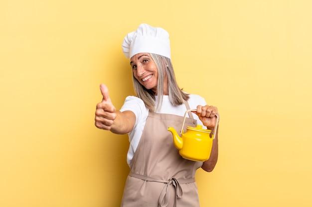 Chef-kokvrouw van middelbare leeftijd die zich trots, zorgeloos, zelfverzekerd en gelukkig voelt, positief lacht met duimen omhoog en een theepot vasthoudt