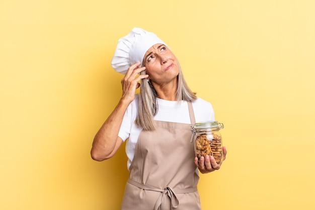 Chef-kokvrouw van middelbare leeftijd die zich verbaasd en verward voelt, hoofd krabt en opzij kijkt met koekjes