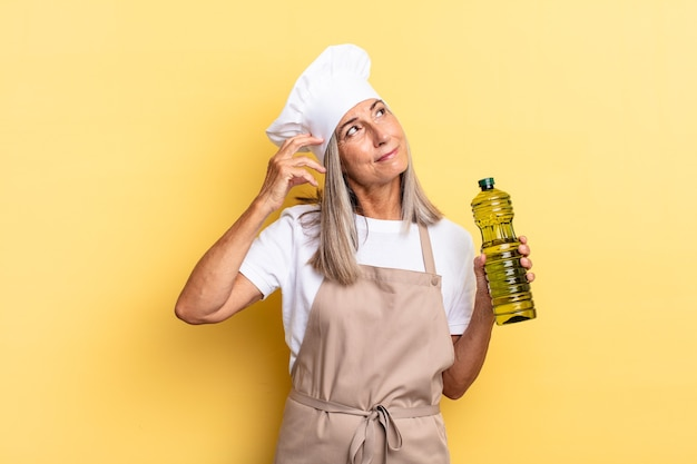 Chef-kokvrouw van middelbare leeftijd die zich verbaasd en verward voelt, hoofd krabt en opzij kijkt