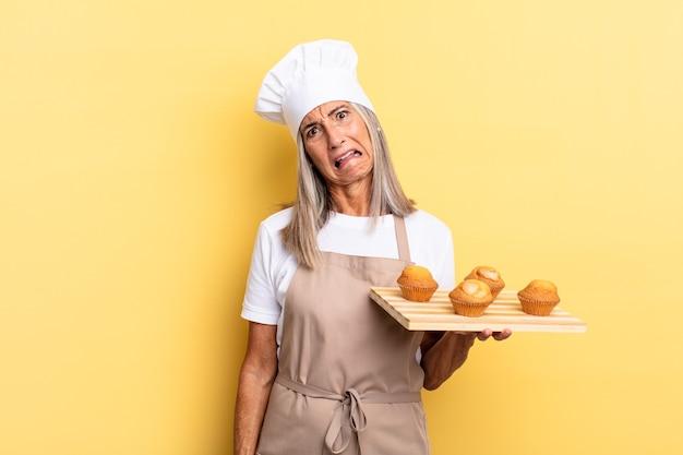 Chef-kokvrouw van middelbare leeftijd die zich verbaasd en verward voelt, met een stomme, verbijsterde uitdrukking die naar iets onverwachts kijkt en een dienblad met muffins vasthoudt