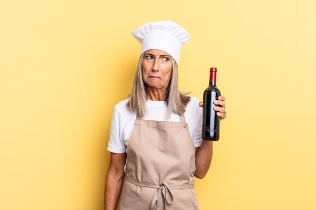 Chef-kokvrouw van middelbare leeftijd die zich verbaasd en verward voelt, met een stomme, verbijsterde uitdrukking die naar iets onverwachts kijkt en een wijnfles vasthoudt