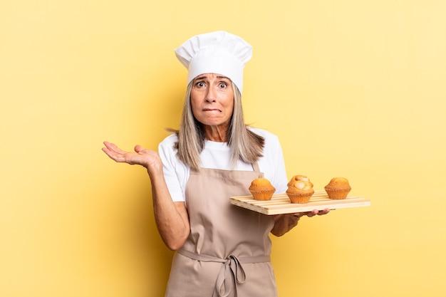 Chef-kokvrouw van middelbare leeftijd die zich verbaasd en verward voelt, twijfelt, weegt of verschillende opties kiest met grappige uitdrukking en een muffinsblad vasthoudt