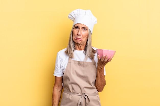 Chef-kokvrouw van middelbare leeftijd die zich verdrietig en zeurderig voelt met een ongelukkige blik, huilt met een negatieve en gefrustreerde houding en een lege pot vasthoudt