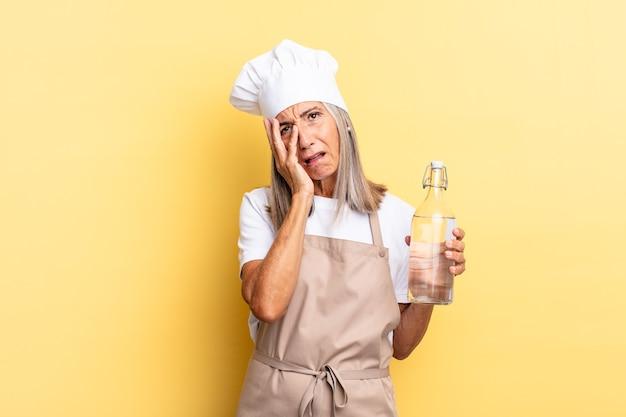 Chef-kokvrouw van middelbare leeftijd die zich verveeld, gefrustreerd en slaperig voelt na een vermoeiende, saaie en vervelende taak, gezicht met de hand vasthoudend met een waterfles