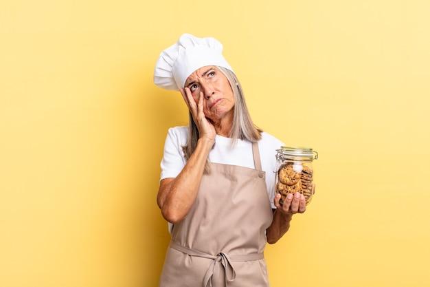 Chef-kokvrouw van middelbare leeftijd die zich verveeld, gefrustreerd en slaperig voelt na een vermoeiende, saaie en vervelende taak, gezicht met de hand vasthoudend met koekjes Premium Foto