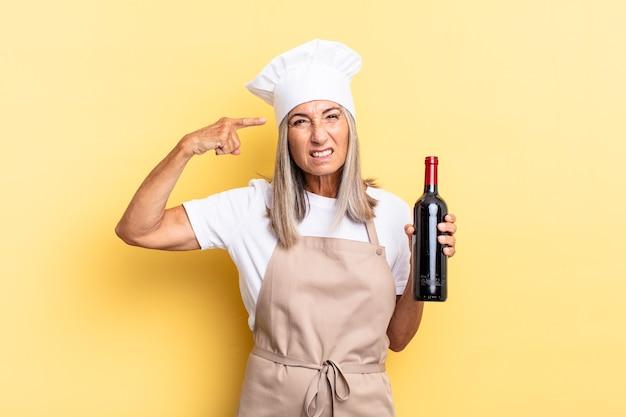 Chef-kokvrouw van middelbare leeftijd die zich verward en verbaasd voelt en laat zien dat je gek, gek of gek bent met een wijnfles