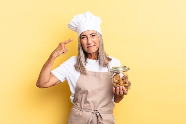 Chef-kokvrouw van middelbare leeftijd die zich verward en verbaasd voelt en laat zien dat je gek, gek of gek bent met koekjes