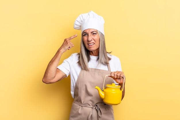 Chef-kokvrouw van middelbare leeftijd die zich verward en verbaasd voelt, laat zien dat je gek, gek of gek bent en een theepot vasthoudt