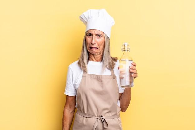 Chef-kokvrouw van middelbare leeftijd die zich verward en verward voelt, met een stomme, verbijsterde uitdrukking die naar iets onverwachts kijkt met een waterfles